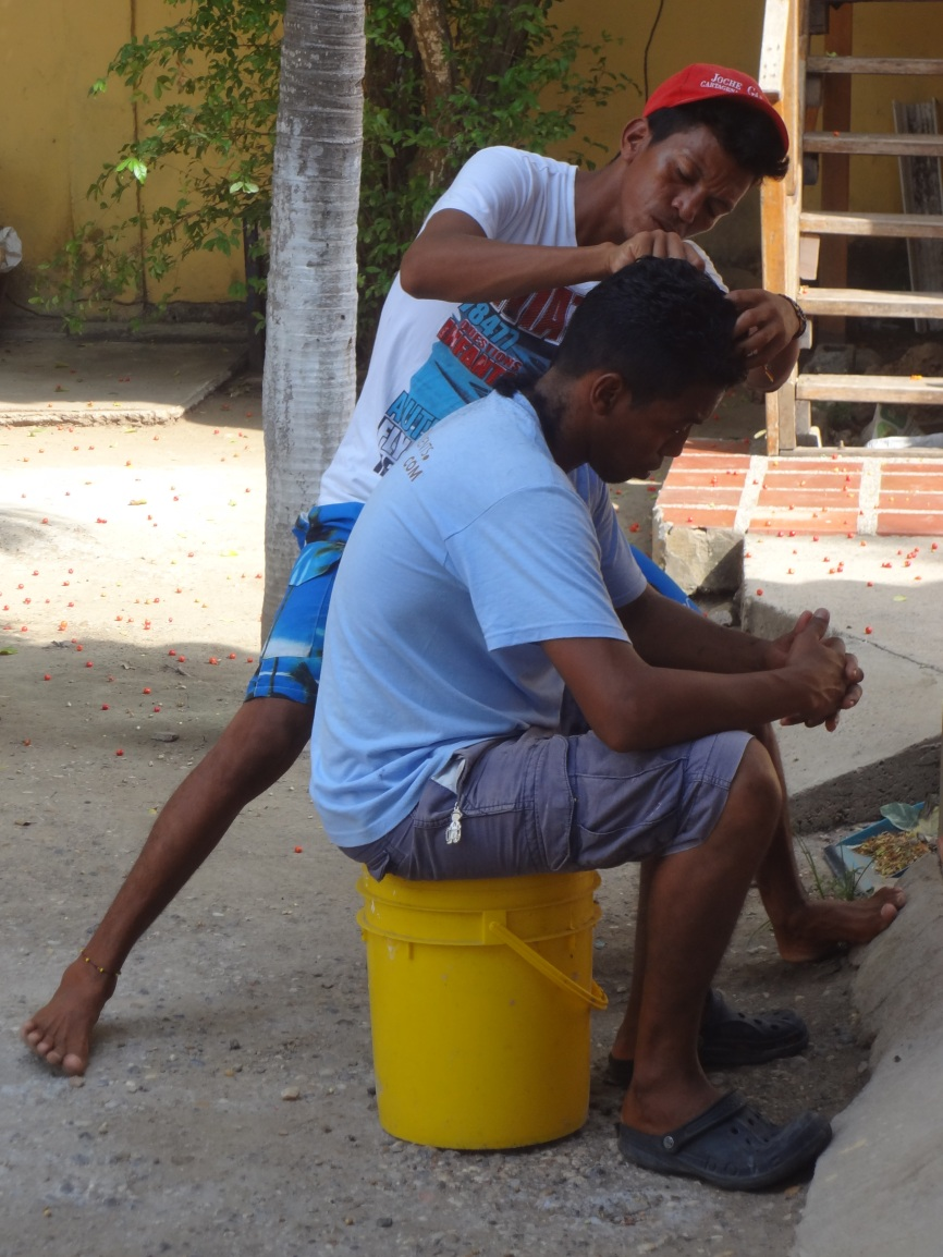 Samy getting his hair cut by his brother.